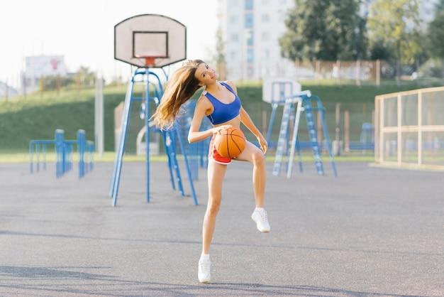 Esbelta garota atlética em tiros curtos e top joga com uma bola de basquete no playground