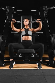 Esbelta, menina fisiculturista, faz os exercícios para os braços na academia. conceito de esportes, queima de gordura e estilo de vida saudável.