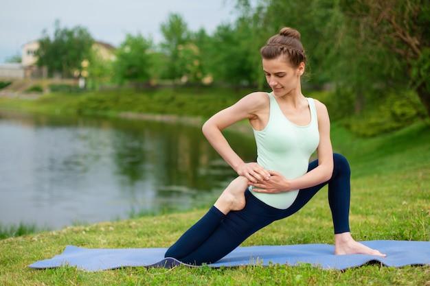 Esbelta menina morena caucasiana fazendo yoga no verão em um gramado verde junto ao rio