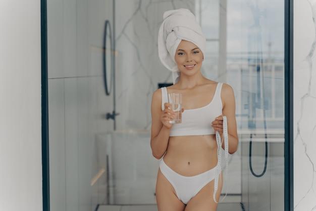 Esbelta mulher atlética feliz em roupa íntima branca clássica em pé no banheiro após a rotina do banho com fita métrica em uma mão e segurando um copo de água na outra, conceito de estilo de vida saudável