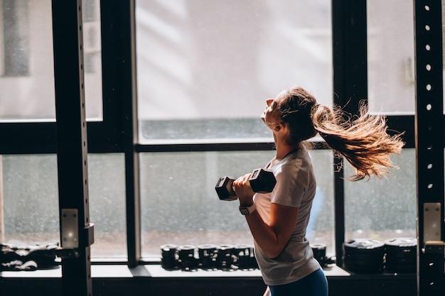 Esbelta mulher atlética realiza exercícios físicos com halteres