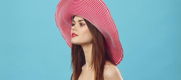 Esbelta mulher bonita está se preparando para férias e recolhe uma mala, uma mala amarela, um chapéu de maiô, uma imagem para férias, estúdio
