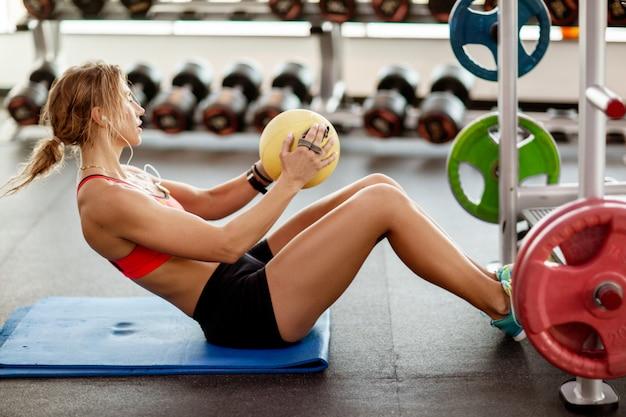 Esbelta mulher bonita no sportswear faz exercícios para a imprensa em um tapete de fitness com uma bola no ginásio