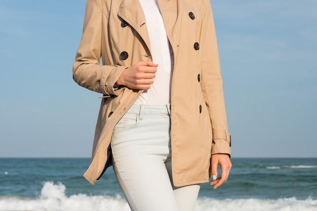 Esbelta mulher de casaco e jeans caminhando ao longo da costa no sol de noite