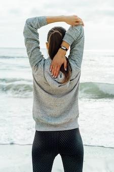 Esbelta mulher no sportswear fazendo alongamento na praia pela manhã