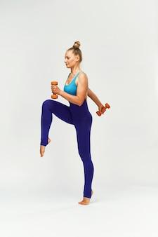 Esbelta mulher no sportswear realiza exercícios com halteres