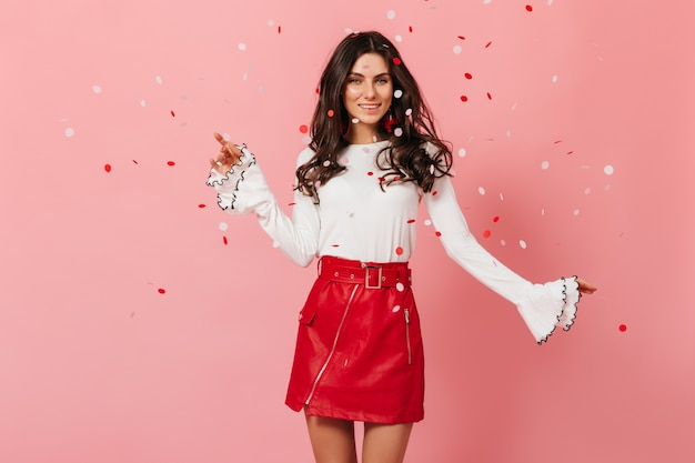 Esbelta senhora de ótimo humor está dançando no fundo rosa com confete. menina com saia de couro com sorriso posando.