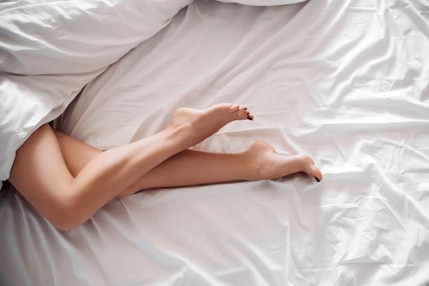 Esbeltas pernas lisas de uma jovem garota sexy em um lençol branco em cima da cama no quarto