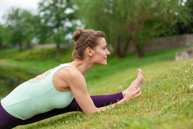 Esbelto jovem morena iogue executa exercícios de ioga desafiadores na grama verde no verão no contexto da natureza