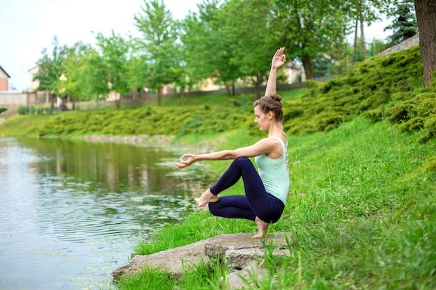 Esbelto jovem morena iogue executa exercícios desafiadores de ioga na grama verde no verão, contra o pano de fundo da natureza