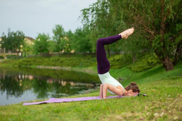 Esbelto jovem morena iogue executa exercícios desafiadores de ioga na grama verde no verão