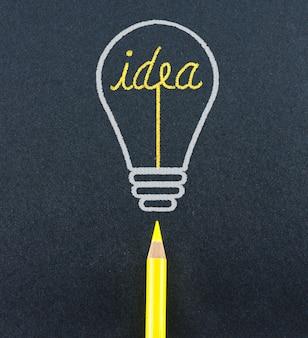 Esboço de lápis amarelo na forma da lâmpada invade a palavra idéia em papel de artesão preto