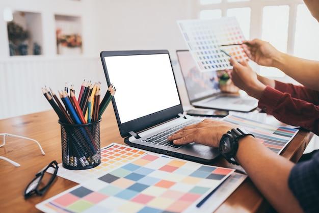 Esboços de desenho de colegas asiáticos desenha no laptop gráfico.