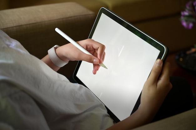 Esboços do desenho da mão da menina com a tabuleta moderna de superfície do écran sensível ao sentar o sofá.