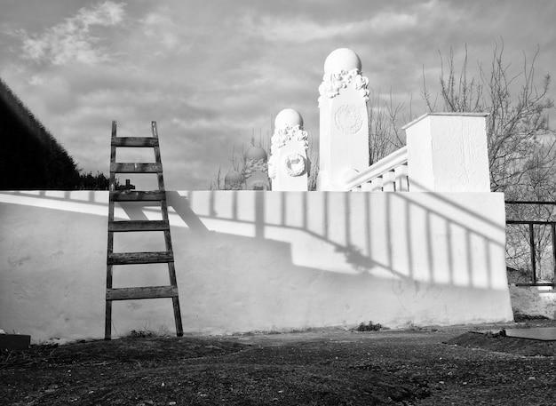 Escada apoiada contra uma parede branca