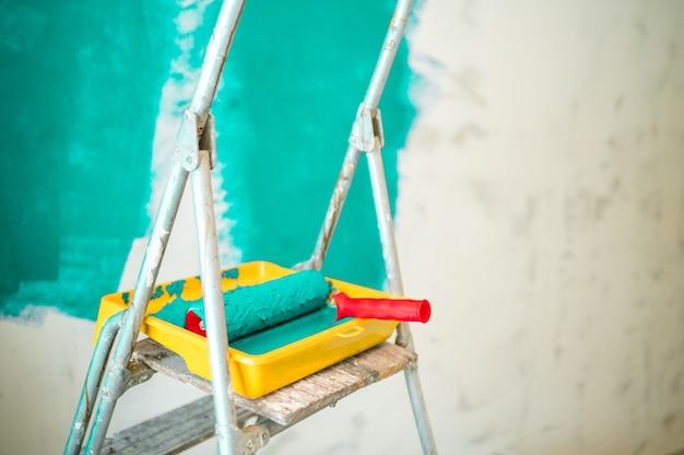 Escada, bandeja de tinta e rolo no fundo de uma parede turquesa sem pintura