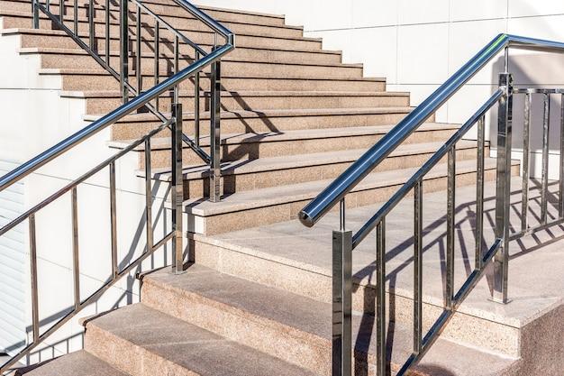 Escada com degraus de granito e corrimão de metal