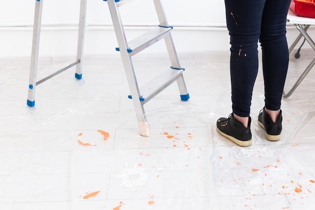 Escada com tinta em um balde perto da parede colorida dentro de casa. renovação e redecoração.
