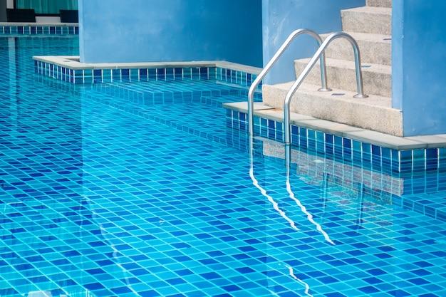 Escada da piscina com água azul