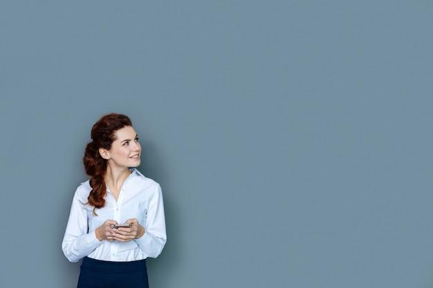 Escada de carreira. mulher inteligente simpática e alegre sorrindo e furando o smartphone enquanto trabalhava no escritório