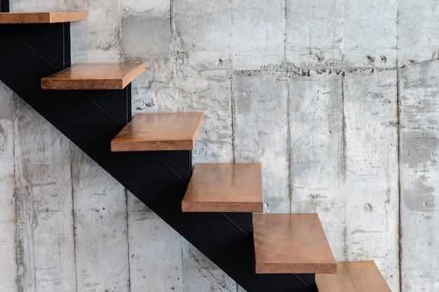 Escada de estrutura moderna com passo de madeira e fundo de textura de concreto