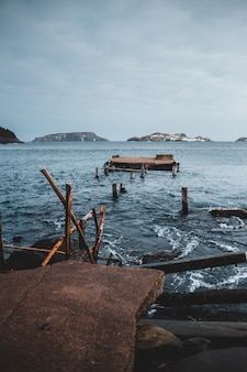 Escada de madeira marrom na rocha marrom perto do corpo d'água durante o dia