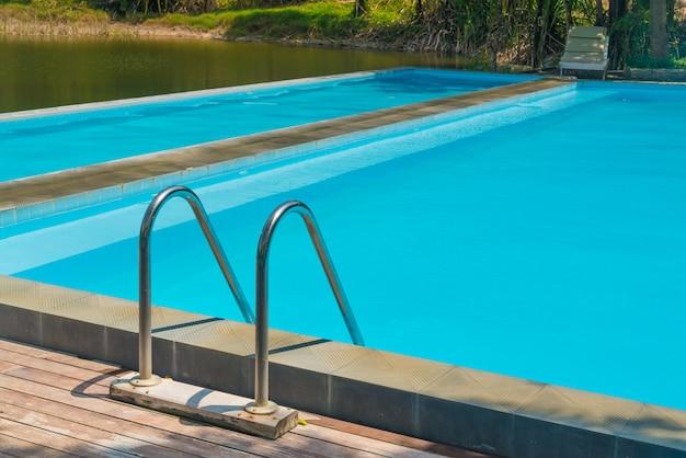 Escada de piscina com piso de madeira no resort.