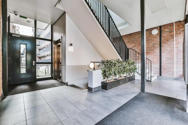 Escada e elevador localizados perto da porta e da parede de tijolos no corredor de um prédio de apartamentos contemporâneo