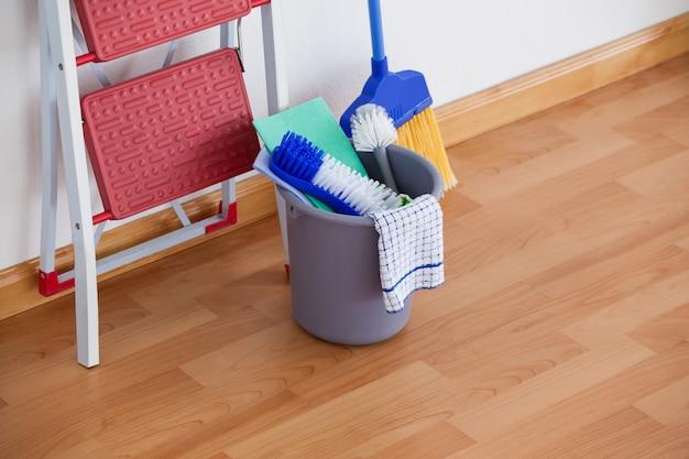 Escada e equipamento de limpeza no piso de madeira
