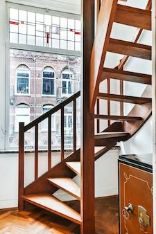 Escada em espiral de madeira elegante conectando níveis de apartamentos residenciais em um edifício de estilo vintage