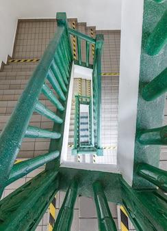 Escada em espiral de retângulo verde na construção contemporânea