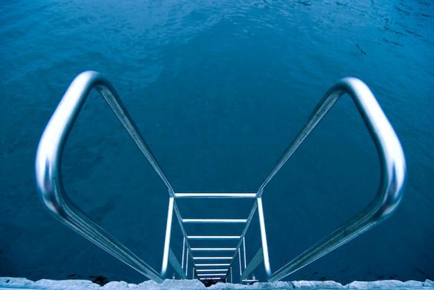 Escada metálica com corrimão na piscina