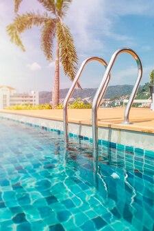 Escada metálica para a piscina. piscina na cobertura em dia de sol