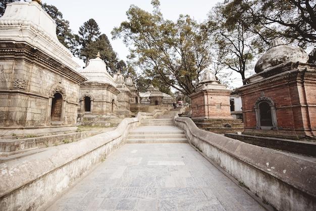 Escada no meio de pequenas estruturas em um templo hindu no nepal
