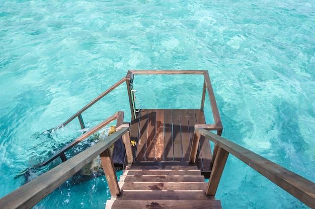 Escada para baixo para oceano cristalino da varanda privada villa de água