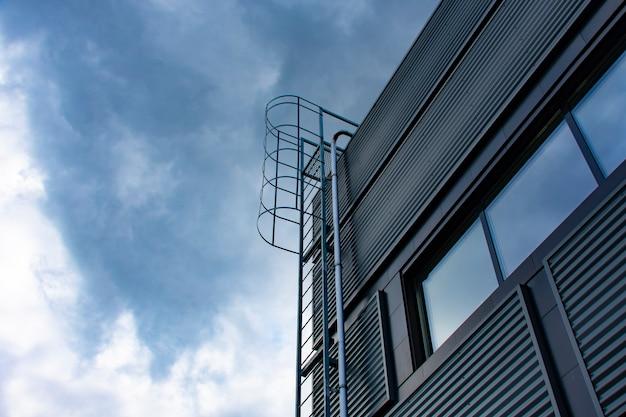 Escada para o céu. escada de metal no edifício no contexto do céu e das nuvens.