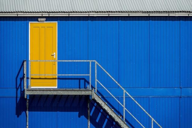 Escada perto da parede azul de uma garagem que leva à porta amarela
