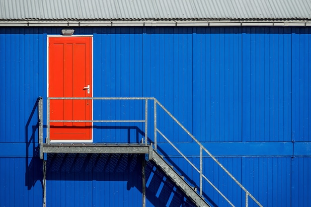 Escada perto da parede azul de uma garagem que leva à porta vermelha