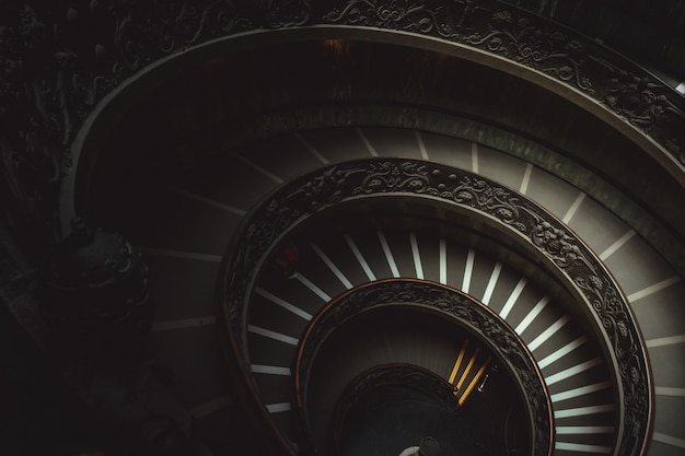 Escada redonda em um museu do vaticano, levando visitantes a ver obras de arte cristãs
