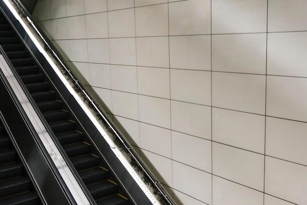 Escada rolante com parede de azulejos em branco