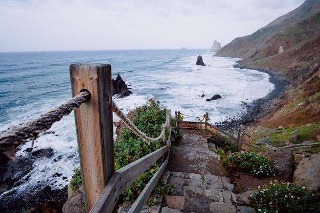 Escada rústica descendente que leva à costa de uma montanha