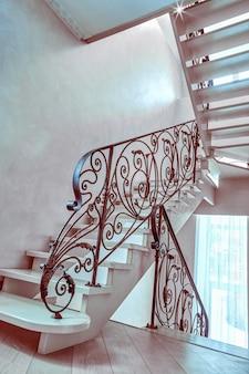 Escadaria com corrimão de ferro forjado em uma casa vazia