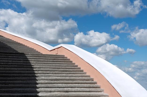 Escadaria concreta contra o céu azul e as nuvens.