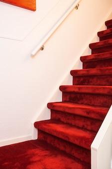 Escadaria de mármore interior moderna com tapete vermelho.