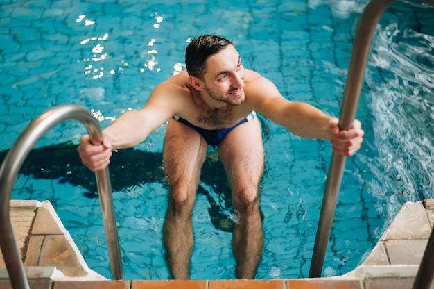 Escadas da piscina do ósmio do homem do ângulo alto