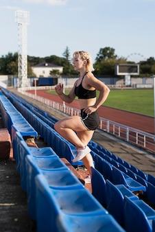Escadas de jovem exercício no estádio