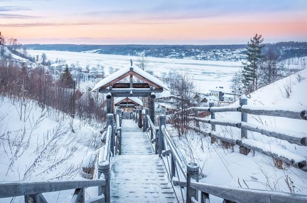 Escadas de madeira do monte levitan e vista do rio volga congelado em plyos na neve sob a luz do sol de inverno.