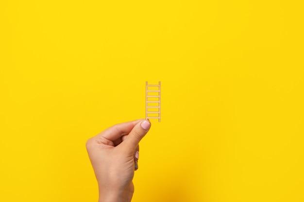 Escadas de madeira nas mãos sobre fundo amarelo, conceito de crescimento de carreira