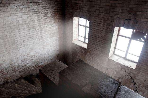 Escadas em um complexo abandonado com luz dramática.