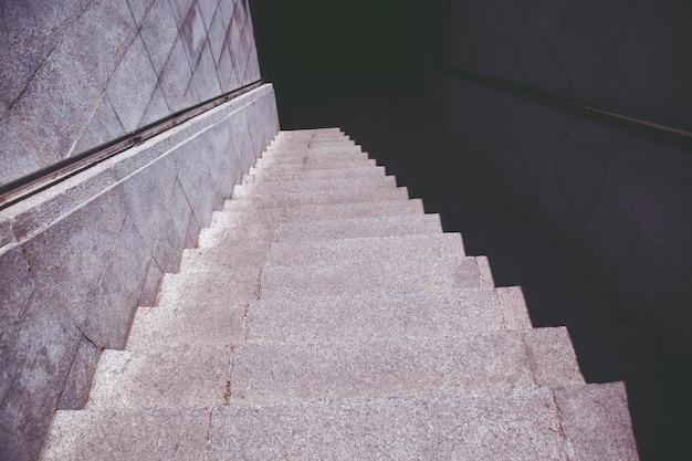 Escadas. escada de metrô velha na noite escura isolada, escadas de concreto na cidade, degraus de pedra de granito frequentemente vistos em monumentos e pontos de referência, descendo. detalhes arquitetônicos de interiores